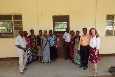 glueckliche Lehrer und Lehrerinnen vor dem renovierten Gebaeude